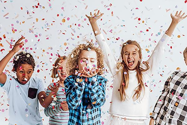 Children launching surrounded by confetti
