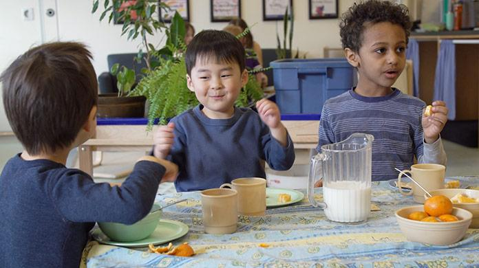 Picture of three pre-school boys sitting around a table eating a snack